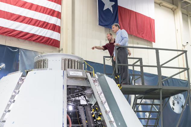 Jon Olansen, project manager for the Ascent Abort-2 crew module, shows Mark Kirsch, Orion Program Manager, progress on the test article in Building 9S. Image Credit: NASA
