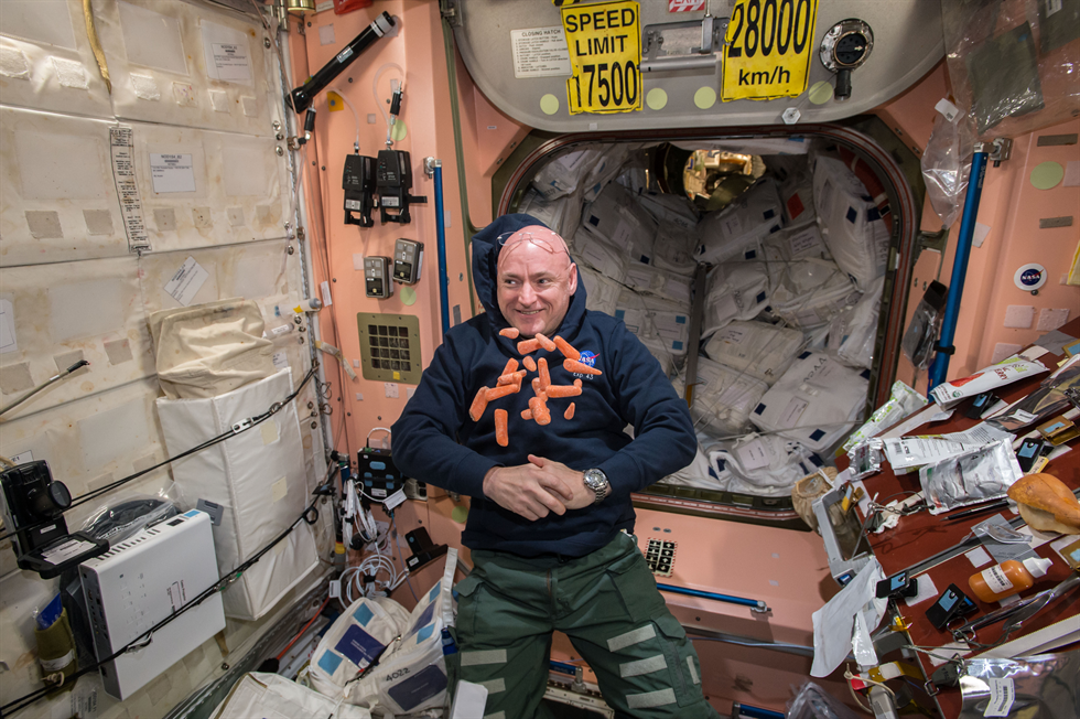 Kelly is photographed with carrots floating around him in the Node 1 module Image Credit NASA