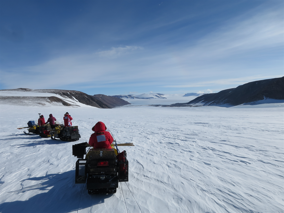 Aboard snow machines, the team traverses a pass toward the blue ice field in the distance. Image Credit: NASA/Cindy Evans