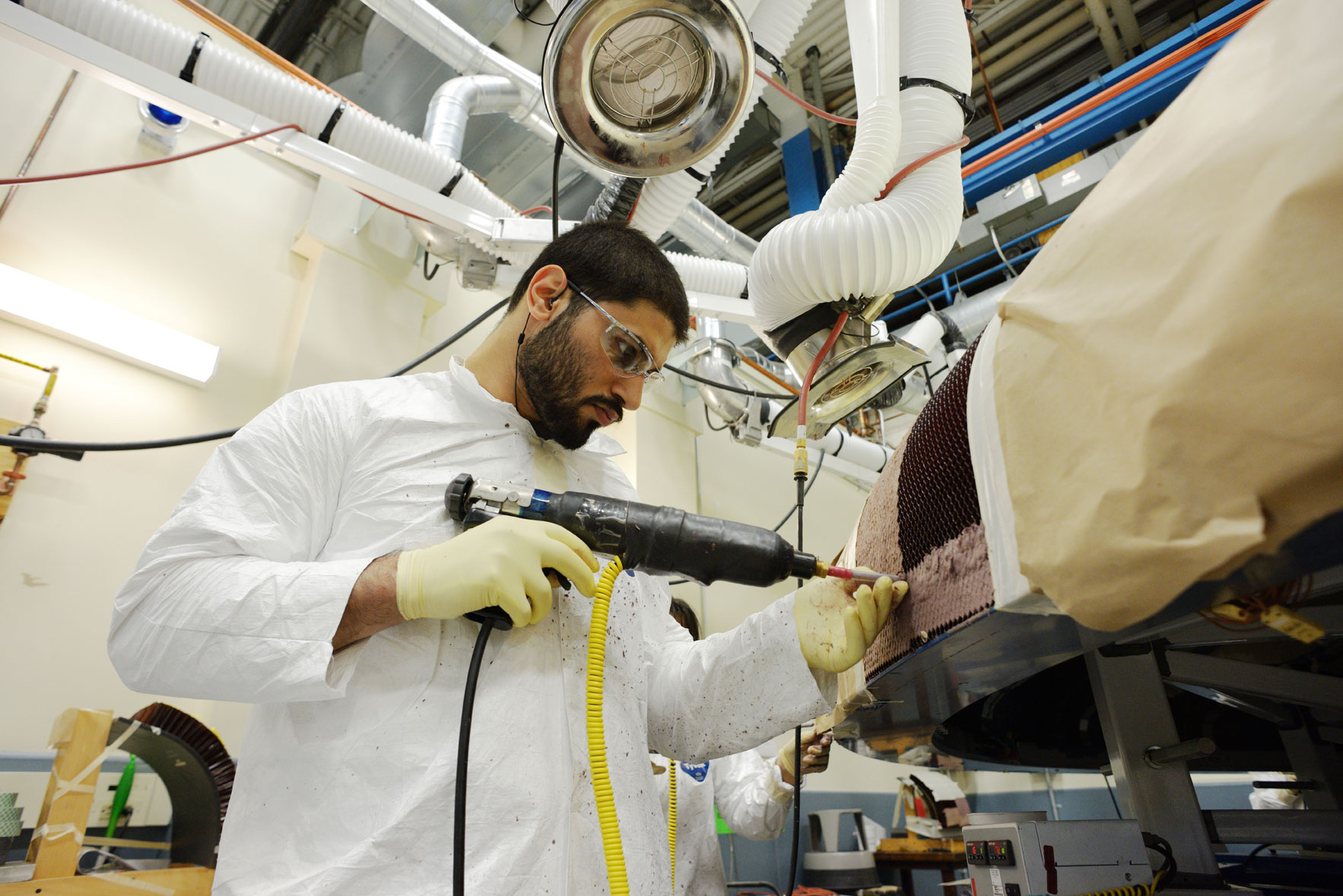 "Textron technicians apply the Avcoat material by ""gunning"" the material into each of the 330,000 individual cells of the honeycomb structure. Image Credit: NASA"