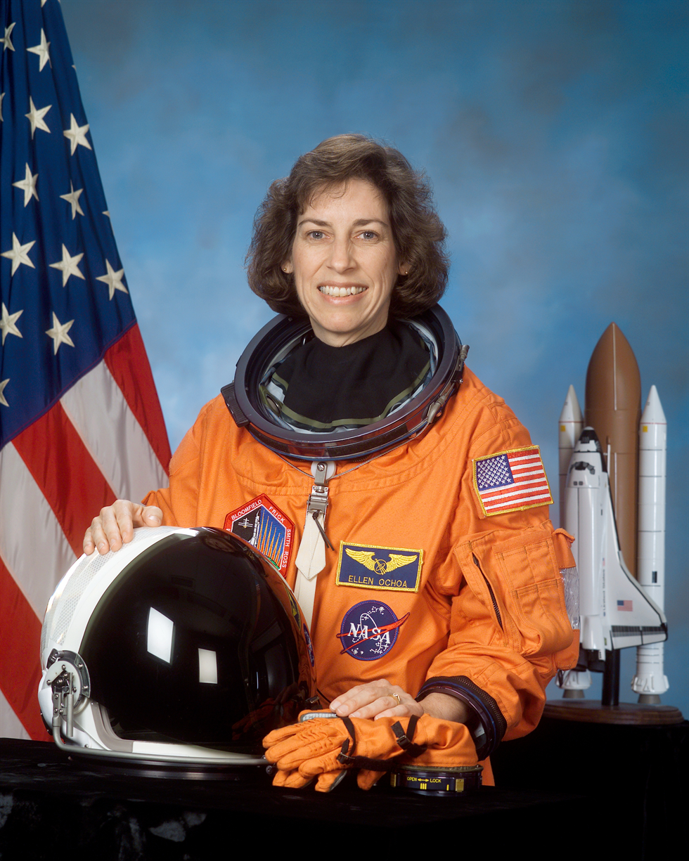 Portrait of astronaut Ellen Ochoa in her orange Launch and Entry Suit with her helmet on the table in front of her and an American flag and a shuttle model in the background. Image Credit: NASA
