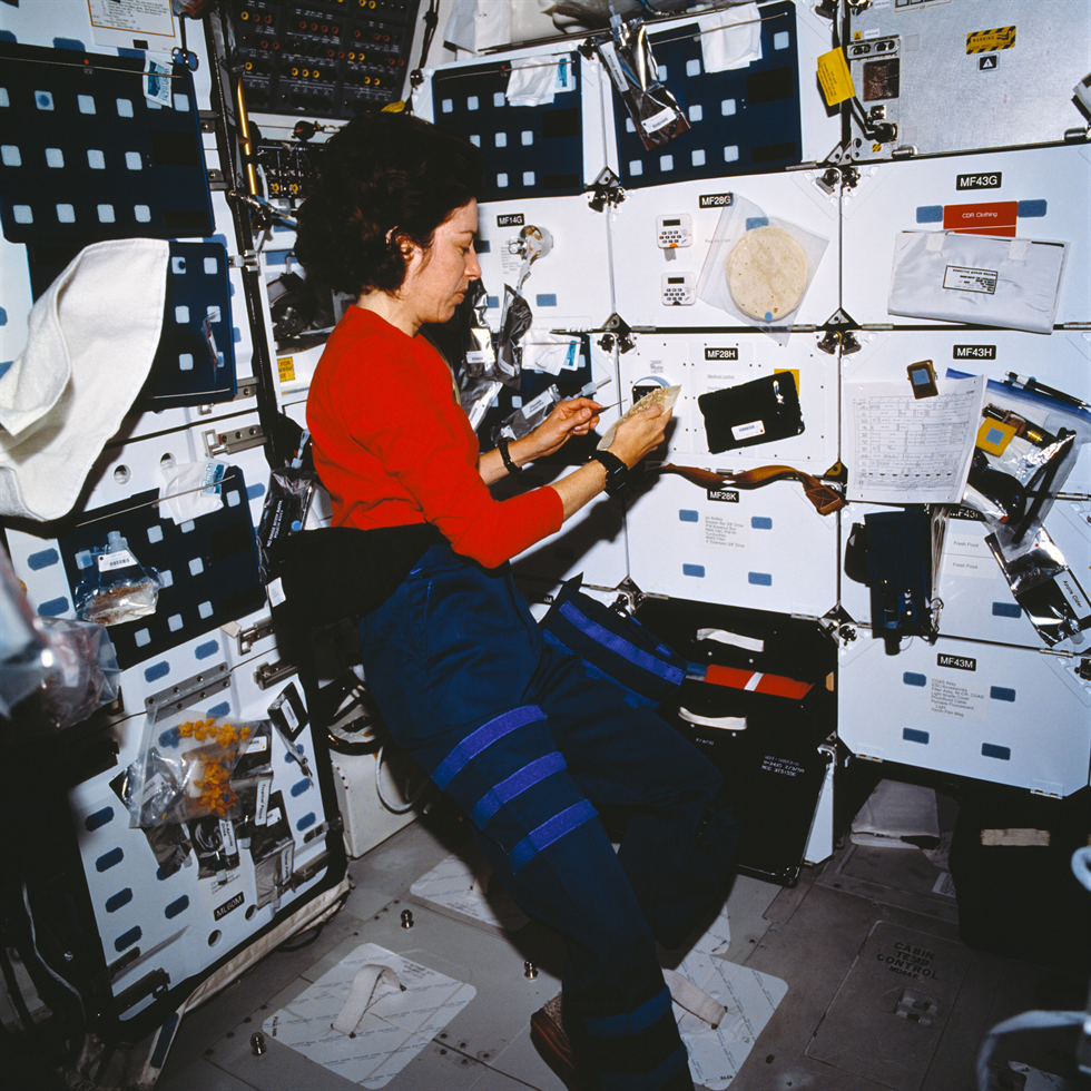 Ochoa prepares a meal on the middeck of Atlantis during the STS-110 mission. Image Credit: NASA