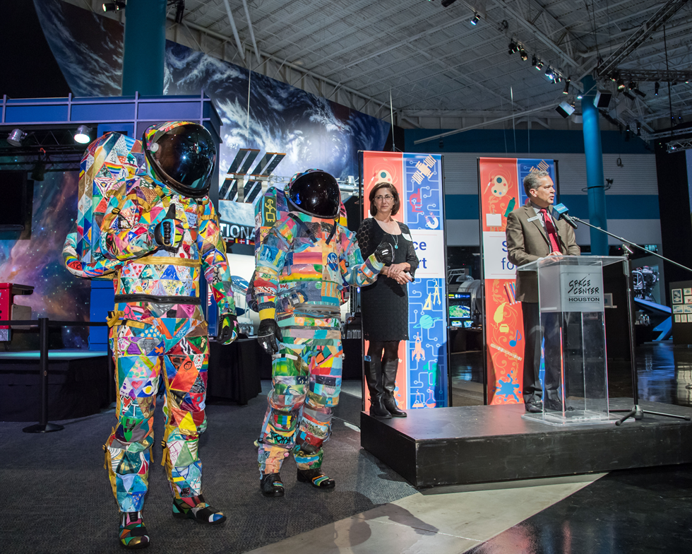 Spacesuits Hope and Unity make a colorful entrance while William T. Harris, president of Space Center Houston, speaks at the podium. With him is the mastermind behind the exhibit concept, retired astronaut Nicole Stott. Image Credit: NASA/Bill Stafford