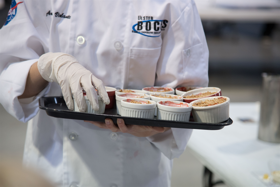 Angelina Violante, Ulster County Boces Career and Technical Center culinary team member, serves Strawberry Rhubarb Crisp to the judges during the Culinary Challenge at Space Center Houston. Image Credit: NASA/Allison Bills