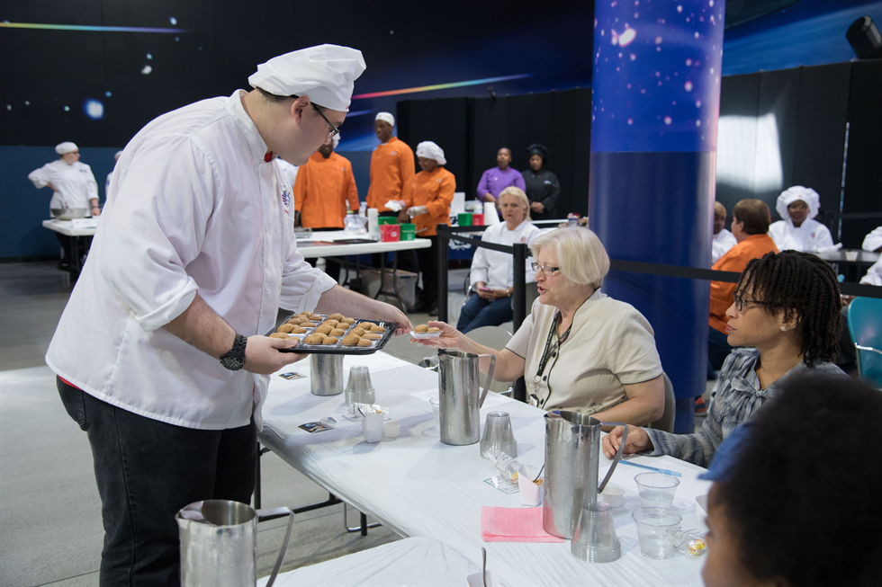 Vickie Kloeris, NASA food scientist and International Space Station food system manager, prepares to taste one of the dessert entries during the Culinary Challenge. Image Credit: NASA/Allison Bills
