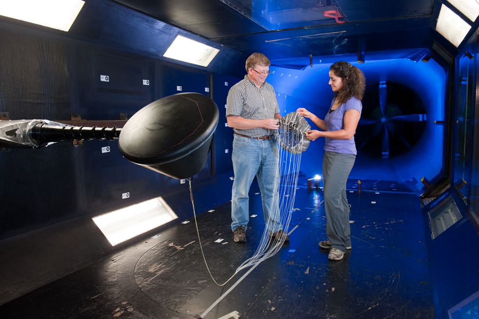 Donn Liddle, a photogrammetrist in NASA Johnson Space Center's Astromaterials Research and Exploration Science Division, along with parachute designer Dr. Anita Sengupta, test a scale model of the Orion spacecraft and its parachute system in the low-speed wind tunnel at Texas A&M University. Image Credit: NASA/James Blair