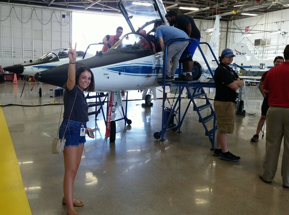 NASA Armstrong intern Annalise Giuliani poses with a NASA T-38 Talon trainer aircraft during an intern tour of Ellington Field in Houston. Image Credit: NASA/Kylie Vandenson