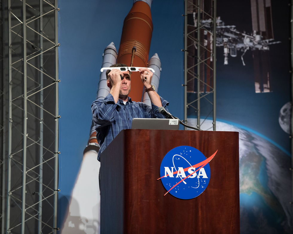 Dr. Tyson Brunstetter, U.S. Navy optometrist, demonstrates how to use solar eclipse viewing glasses. Image Credit: NASA/Robert Markowitz