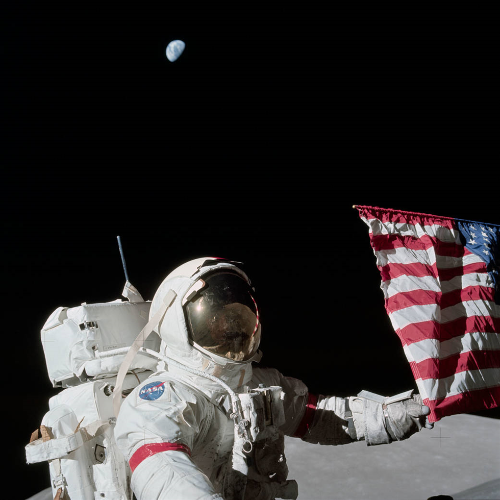 Apollo 17 commander Eugene A. Cernan is holding the lower corner of the American flag during the mission's first EVA, December 12, 1972. Photograph by Harrison J.
