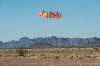 An Orion test capsule with its three main parachutes touches down in the Arizona desert Sept. 12. Credit: NASA