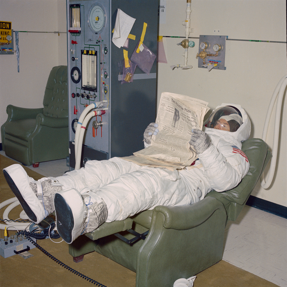 Backup Apollo 11 Commander James A. Lovell reads a newspaper while waiting to enter the altitude chamber. Image Credit: NASA