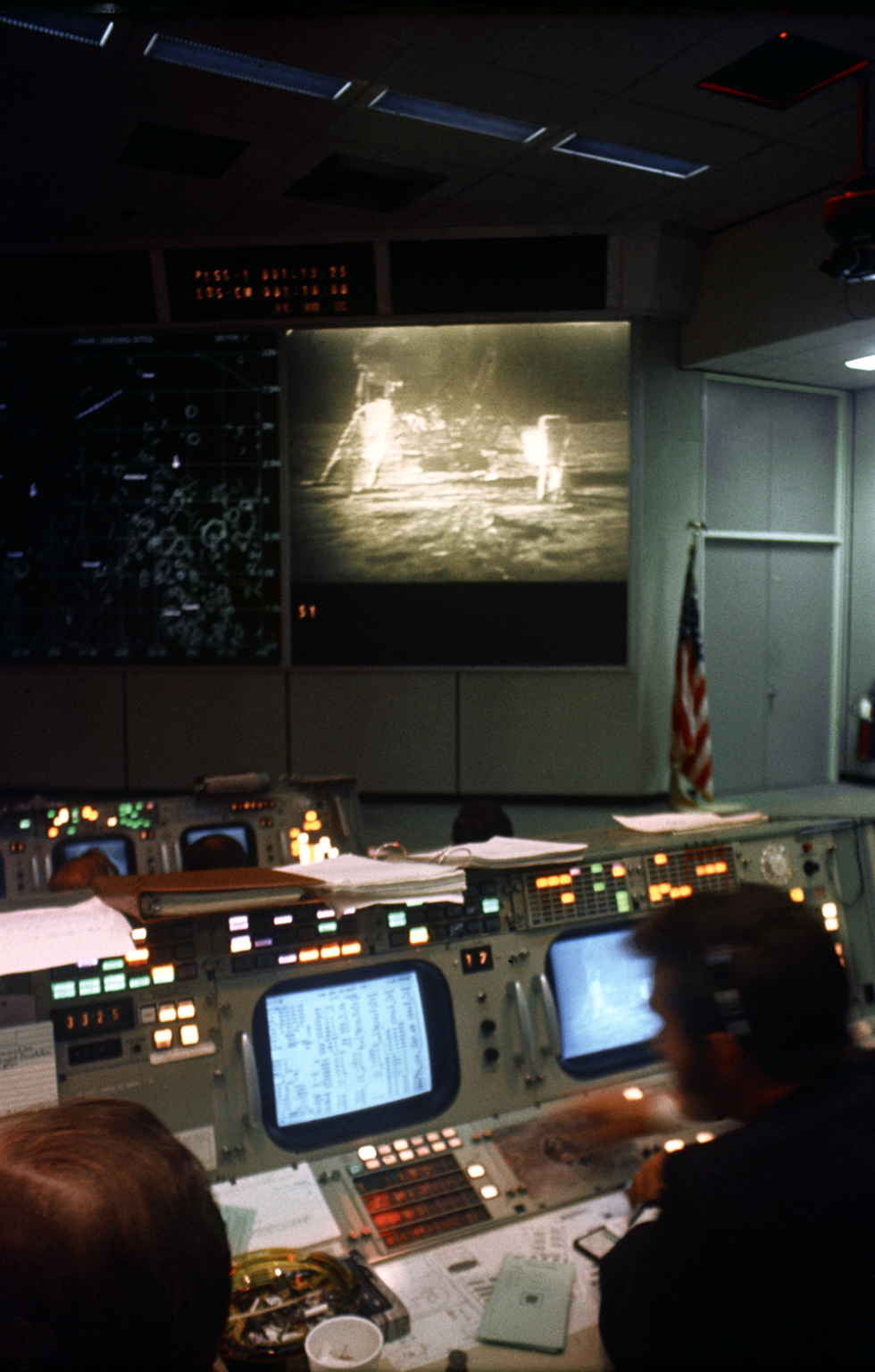 Interior view of the Mission Control Center during the Apollo 11 lunar spacewalk. The TV monitor shows astronauts Neil Armstrong and Buzz Aldrin on the surface of the Moon. Image Credit: NASA