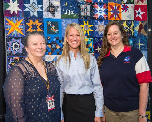 From left, Vicki Magnum with Quilts, Inc., Nyberg and Stacey Menard. Image Credit: NASA/Lauren Harnett