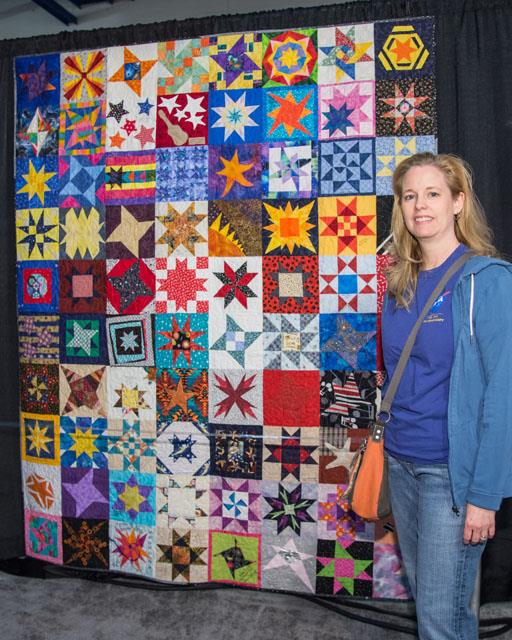 Maura White, a JSC volunteer instrumental in getting the quilt project to the International Quilt Festival, poses in front of one of the creations. Image Credit: NASA/Lauren Harnett