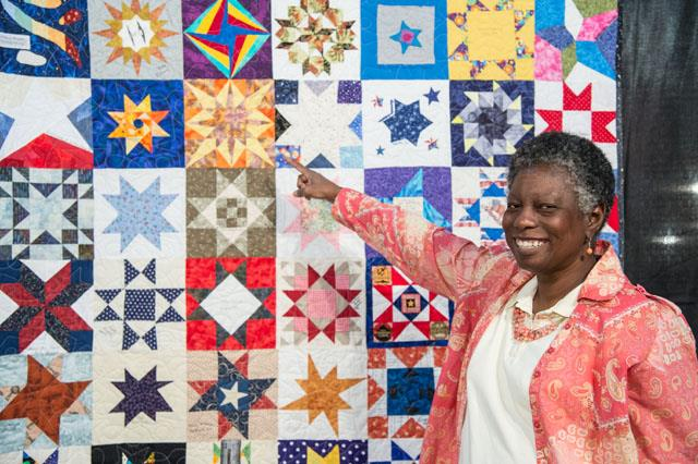 A contributer to the Astronomical Quilt Project proudly points out her square. Image Credit: NASA/Lauren Harnett